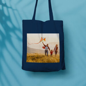 An image of a tote bag with a photo printed on the side of it. The photo is of a family running and flying a kite.