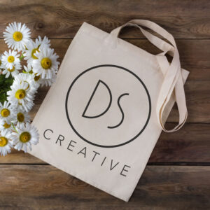 An image of a rustic, eco-friendly tote bag. The DS Creative logo is printed on the side and the fabric is unprocessed.